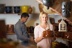Female customer in ceramics workshop. Cheerful female customer picking crockery in ceramics workshop stock photos