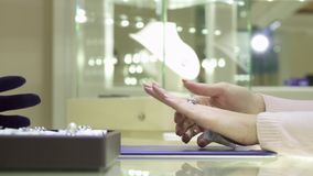 Female customer chooses ring at the jewelry boutique. Close up of female customer choosing ring at the jewelry boutique. Woman`s hand trying on different finger Royalty Free Stock Photo