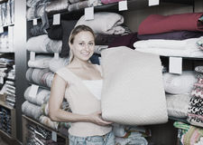 Female customer choosing blanket. In bedding section in shop Royalty Free Stock Photos