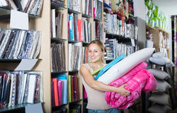 Female customer choosing blanket and pillow. Portrait of female customer choosing blanket, pillow and textile in bedding section in shop Royalty Free Stock Image