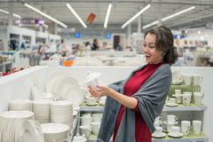 Female customer choosing Ceramic kettlein the supermarket mall. Emotional female customer choosing Ceramic kettle and utensil dishes in the supermarket mall. She Royalty Free Stock Photography