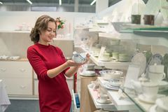 Female customer choosing Ceramic kettlein the supermarket mall. Female customer choosing Ceramic kettle and utensil dishes in the supermarket mall Royalty Free Stock Photography