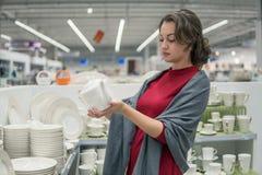 Female customer choosing Ceramic kettlein the supermarket mall Royalty Free Stock Photo