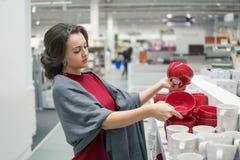 Female customer choosing utensil dishes in the supermarket mall Stock Images
