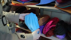 Female customer choosing colored turban at local market, shopping, latest trends. Stock footage stock footage