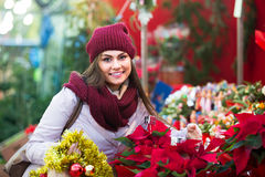 Female customer choosing  decorations. Portrait of female customer 25s choosing eucalyptus decorations for Christmas outdoor Royalty Free Stock Photos