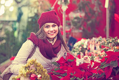 Female customer choosing  decorations. Portrait of female customer 25s choosing eucalyptus decorations for Christmas outdoor Stock Image