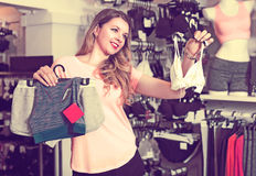 Female customer is choosing sports underwear. In lingerie shop Royalty Free Stock Photo