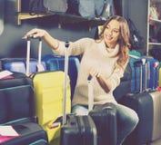Female customer choosing travel suitcase Royalty Free Stock Photography