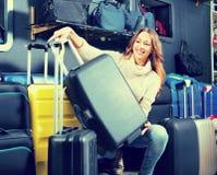 Female customer choosing travel suitcase Royalty Free Stock Image