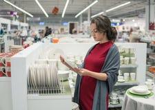 Female customer choosing utensil dishes in the supermarket mall Stock Photos