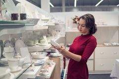 Female customer choosing utensil dishes in the supermarket mall Royalty Free Stock Images