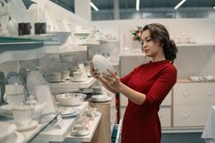 Female customer choosing utensil dishes in the supermarket mall.  Stock Photos