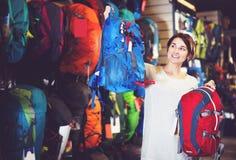 Female customer deciding on new rucksack. Smiling female customer deciding on new rucksack in sports equipment store royalty free stock image