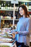 Portrait Of Female Customer In Delicatessen Filling Pot With Green Olives stock images