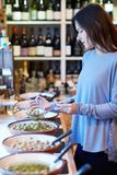 Female Customer In Delicatessen Filling Pot With Green Olives royalty free stock photography