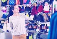 Female customer examining knit caps in sports store Stock Image