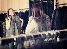 Female customer examining new fur vest Royalty Free Stock Image
