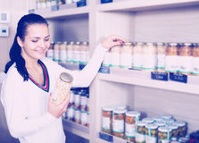 Female customer examining various canned beans. Happy female customer examining various canned beans in grocery shop Royalty Free Stock Photos