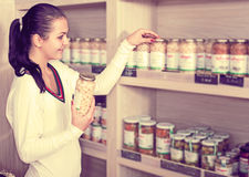 Female customer examining various canned beans Royalty Free Stock Image