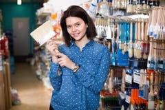 Female customer examining various painting brushes Stock Image