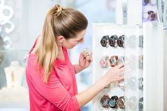 Female customer in store looking for wristwatches. Female customer in fashion store looking for wristwatches Stock Photos