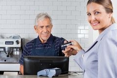 Female Customer Giving Credit Card To Senior Stock Images