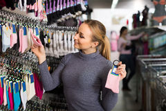 Female customer holding different pair of socks in hands in unde Stock Photography