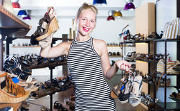 Female customer holding many pair of shoes. Female customer holding many pair of heeled shoes in fashion store stock photos