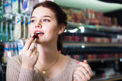 Female customer looking for lipstick in cosmetics shop Royalty Free Stock Images