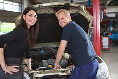 Female Customer with Mechanic. Portrait of happy female customer and mechanic in garage Stock Image