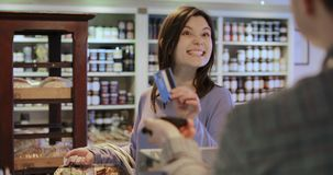 Female customer paying sales assistant for shopping. In delicatessen with contactless credit card stock footage
