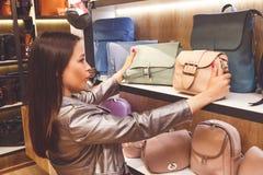 Female customer purchasing new handbag in shop Royalty Free Stock Image
