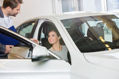 Female customer receiving car key from mechanic in automobile repair shop Stock Photography