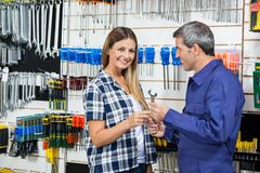Female Customer Receiving Wrench From Customer Royalty Free Stock Image