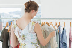 Female customer selecting clothes at clothing rack in store Stock Image