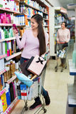 Female customer selecting drugstore products. Glad beautiful smiling female customer selecting drugstore products and standing with shopping trolley royalty free stock photo