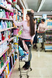 Female customer selecting drugstore products. Glad smiling female customer selecting drugstore products and standing with shopping trolley royalty free stock images