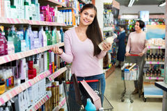 Female customer selecting drugstore products. Positive smiling female customer selecting drugstore products and standing with shopping trolley royalty free stock photography