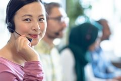 Female customer service executives talking on headset at desk. Side view of Asian female customer service executives talking on headset at desk in office. In the royalty free stock photo