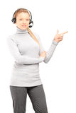 Female customer service operator with headphones pointing with f Stock Image