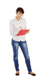 Female Customer Service Representative. Young attractive female customer service representative with headset writing on clipboard, standing on isolated white Stock Photo