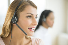 Female Customer Service Representative Looking Away. Happy female customer service representative looking away with colleague in background Stock Image