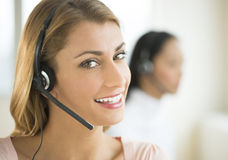 Female Customer Service Representative Smiling. Close-up portrait of female customer service representative smiling with colleague in background Royalty Free Stock Images