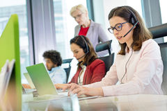 Female customer service representative using laptop while colleagues in background at office Stock Photo