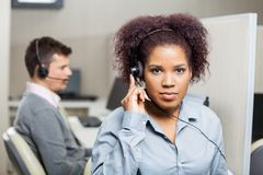 Female Customer Service Representative Using. Portrait of serious female customer service representative using headset with male colleague in background at Royalty Free Stock Photo