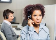 Female Customer Service Representative Using. Serious female customer service representative using headset with male colleague in background at office Stock Image