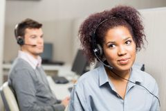 Female Customer Service Representative Wearing. Headset with male colleague in background at office Stock Photos