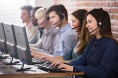Female Customer Services Agent In Call Center. Positive Female Customer Services Agent With Headset Working In A Call Center royalty free stock photo