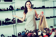 Female customer in shoes center. Portrait of glad female customer doing shopping in shoes center Stock Photos